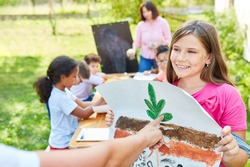 Girl in summer camp for ecology and nature conservation with the drawing of a plant