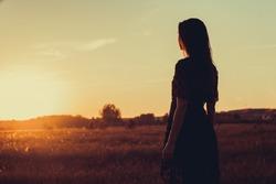 Girl in summer field on sunset background