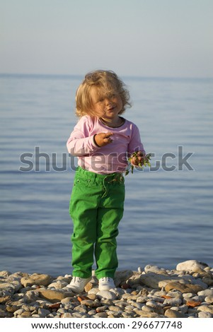 Girl in the autumn at the sea . standing against the evening sea