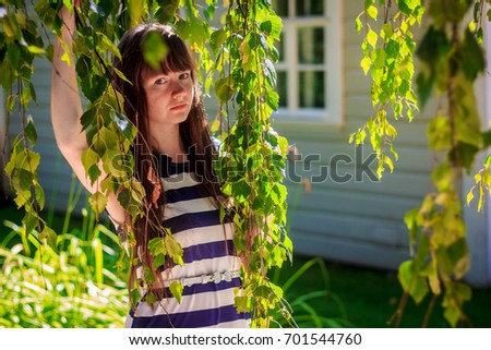 Girl in the branches of a birch #701544760