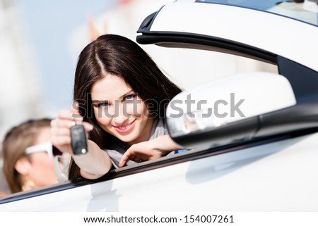 Girl in the car shows car key. Buying car and getting the freedom