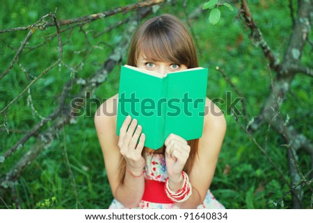 girl in the forest reading a book