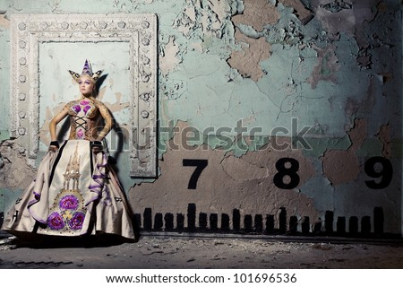 Girl in the image of queen stands near the wall with numbers