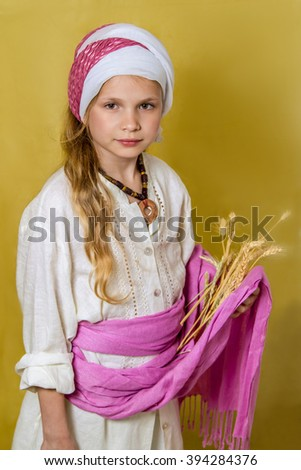 Girl in the image of Ruth the Moabitess holds heads of grain, card for Jewish holiday of Shavuot #394284376