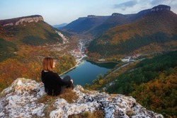Girl in the mountains. Picturesque autumn landscape with mountains and lake. Girl on a mountain cliff admiring the beautiful view.