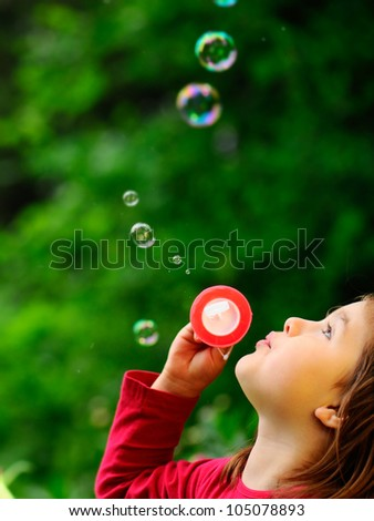 Girl in the park with bubbles.