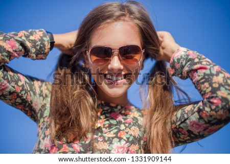 Girl in the spring. Beautiful smiling girl in sunglasses on a background of blue sky. Tourist girl on vacation. Travel and Vacation #1331909144