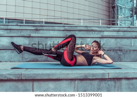 Girl in the summer in city on a yoga mat does exercises on the abs, twisting the abs. Active movement, sports figure and clothes, top leggings, sneakers.