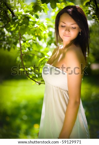 girl in the sun in green in a white dress