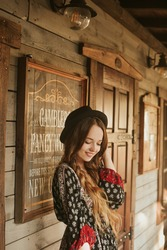 Girl in the Wild West, in Western house. Girl in hat with long cerly hair smile. Beautiful pretty girl in black hat. Incredible trip, travel. Woman on the terrace in red dress pouse.