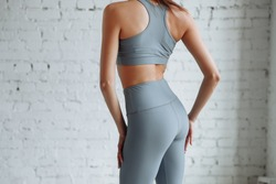 Girl in tight clothes yoga and fitness closeup. Gray leggings with high waist and halter top