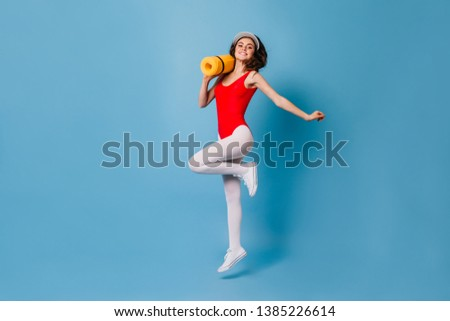 Girl in tight spots suit happily jumps on blue background. 80s woman carries her yellow fitness mat