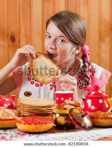 Girl in traditional  clothes eating pancake during  Maslenitsa festival