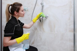 Girl in uniform cleaning the faucet in the shower stall. Napkin and spray in hand.The bathroom is decorated with marble tiles.