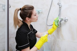 Girl in uniform cleaning the faucet in the shower stall. The bathroom is decorated with marble tiles. The concept of cleanliness and hygiene.