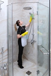 Girl in uniform cleaning the shower stall. Bathroom interior with marble tiles. The concept of cleanliness and hygiene.