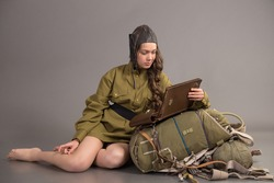 girl in uniform of the Soviet army and aviator cap sits on parachute