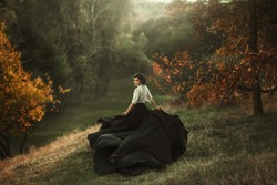 girl in vintage dress running looking around silk skirt train fabric waving flying fluttering wind. Artistic Photography. Vintage clothes medieval woman queen, mysterious lady back. Autumn tree forest