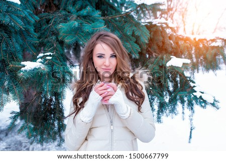 girl in warm jacket stands outside in winter, snow is snowdrifts, a green branch of spruce, in hands of a mug of tea coffee, warms up in morning at winter resort. #1500667799