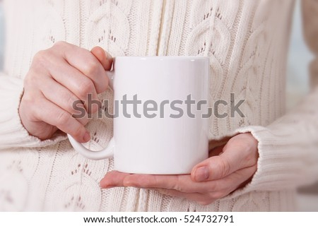 Girl in warm sweater is holding white mug in hands.. Mockup for winter gifts design. #524732791