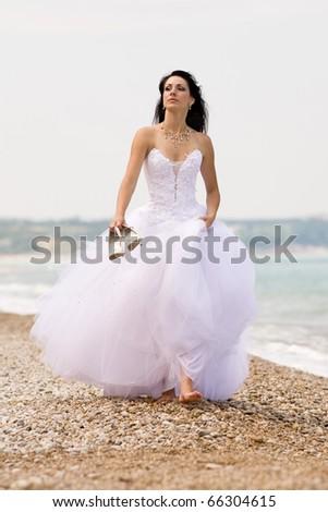 Girl in wedding dress walking along the beach