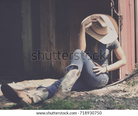 Girl in western wear relaxes in shadows of barn, representing agriculture industry in cowboy hat, jeans and cowboy boots. #718930750