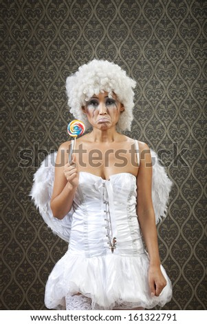 Girl in white angel costume with lollipop left all alone and crying.
