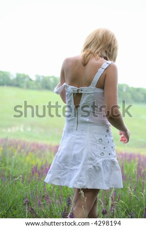 Girl in white dress going away on meadow