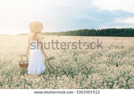 Girl in white dress in a field of yellow flowers blossoming #1065001922