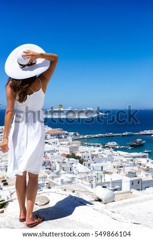 Girl in white dress is looking over Mykonos town, Greece