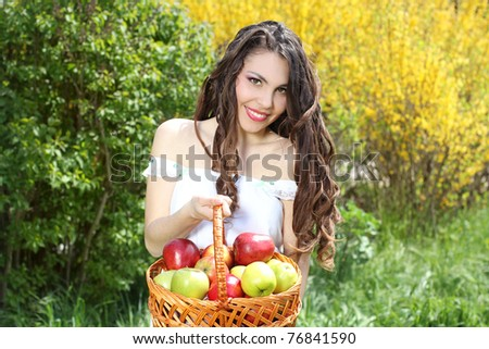 Girl in white dress presents basket of apples