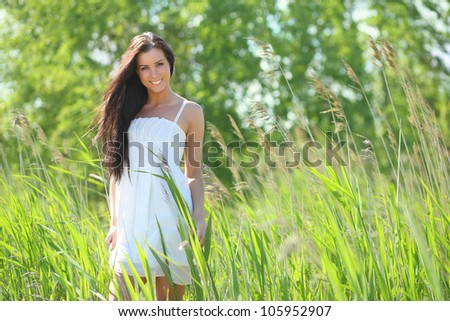 girl in white dress standing in the grass