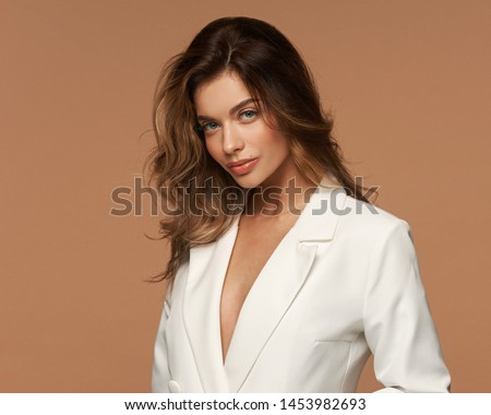 Girl in white suit with loose dry hair and make-up posing on a beige background. Fashion style body length studio portrait. Elegant fashionable woman
