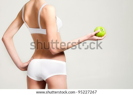 girl in white underwear with a green apple in a cookie