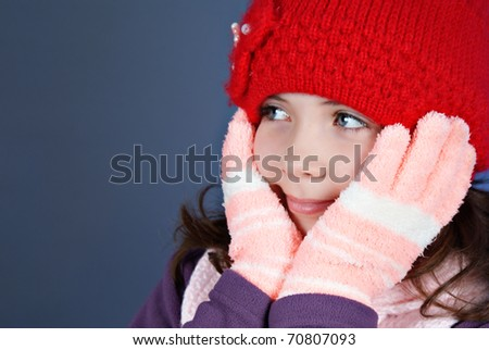 Girl in winter clothes on blue background