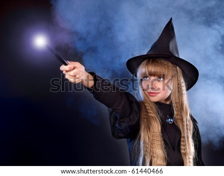 Girl in witch's hat with magic wand casting spells.