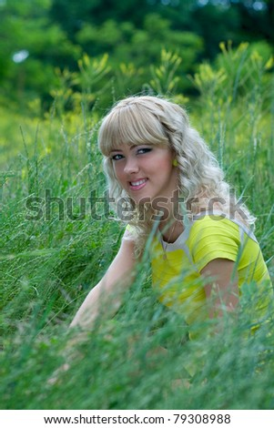 Girl in yellow blouse on green grass.