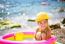 Girl in yellow straw hat plays in outdoor near sea, in water with a bucket in an inflatable pool on the beach. Indelible products to protect children's skin from the sun, sunburn. resort at the ocean.