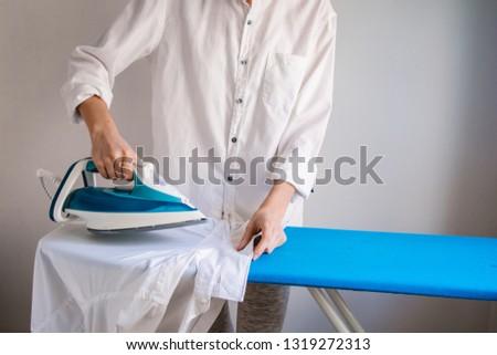 Girl ironing shirt, white shirts, cleaning service #1319272313