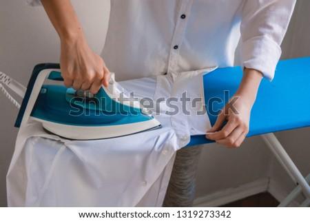 Girl ironing shirt, white shirts, cleaning service #1319273342