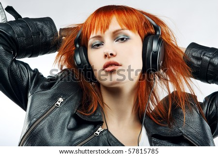 girl is a music lover, red-haired girl in ear-phones - stock photo