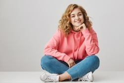 Girl is always happy to hear interesting stories. Curious cheerful woman with curly hair in stylish outfit sitting on floor with crossed legs, leaning on hand, smiling, taking part in conversation