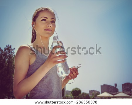 Girl is engaged in sports while listening to music. She is resting and drinking water.