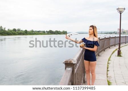 girl is feeding gulls on the embankment of the Angara River #1137399485
