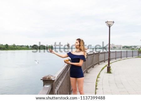 girl is feeding gulls on the embankment of the Angara River #1137399488