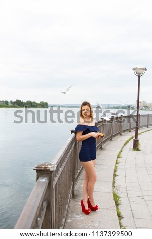 girl is feeding gulls on the embankment of the Angara River #1137399500