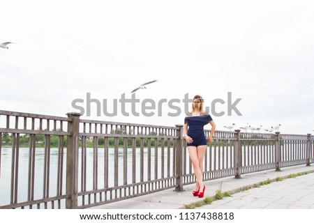 girl is feeding gulls on the embankment of the Angara River #1137438818