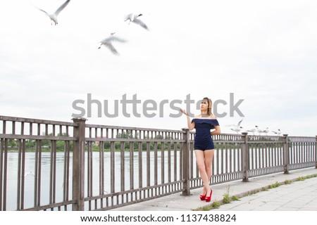 girl is feeding gulls on the embankment of the Angara River #1137438824
