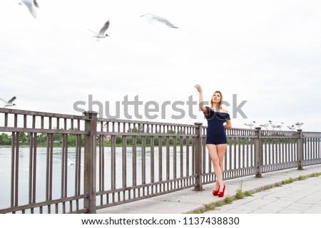 girl is feeding gulls on the embankment of the Angara River #1137438830