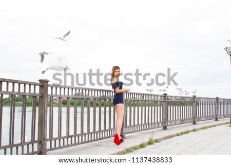 girl is feeding gulls on the embankment of the Angara River #1137438833